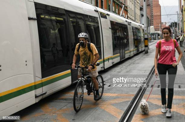 A man with a mask rides a bicycle while a women walks her dog next to the Tranvia in Medellin Antioquia department Colombia on March 15 2018 The...