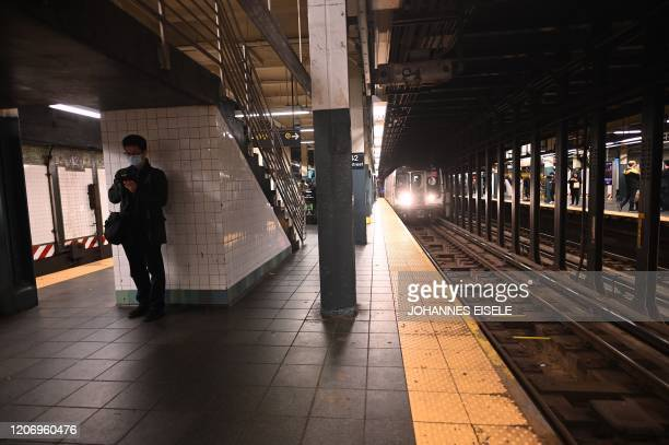 A man with a mask wait for a subway at the Plattform at Times Square on March 13 2020 in New York City The World Health Organization said March 13...