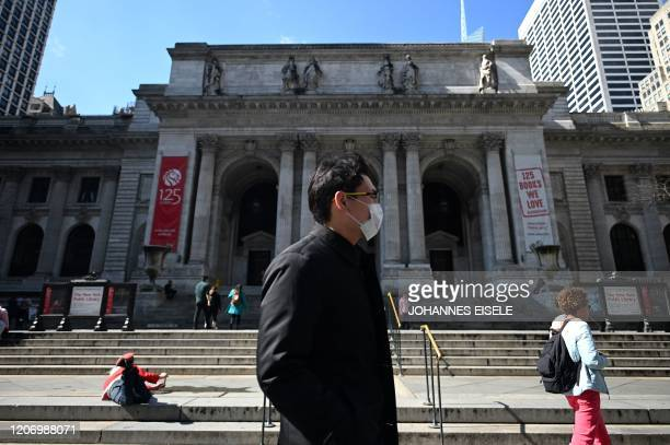 A man with a mask walks past the New York Public Library next to Bryant Park on March 13 2020 in New York City The World Health Organization said...