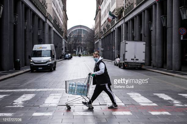 A man with a mask with a shopping cart in the deserted Via Roma in Turin during on the Italy Continues Nationwide Lockdown To Control Coronavirus...