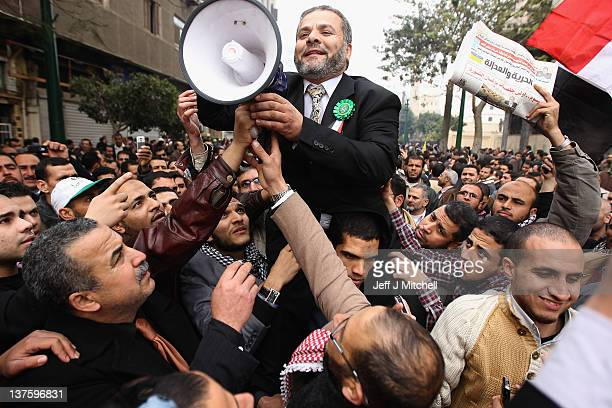 A man with a megaphone is lifted on up as the Muslim Brotherhood gather outside the Egyptian Parliament on January 23 2012 in Cairo Egypt The session...