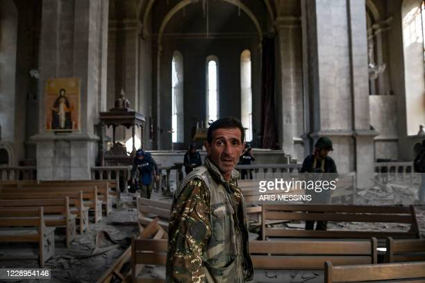 Man with a military outfit stands as journalists report on October 8, 2020 inside the damaged Ghazanchetsots Cathedral in the historic city of...