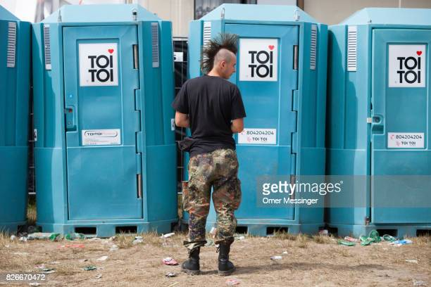 A man with a mohawk haircut is waiting outside the chemical toilets at the 2017 Woodstock Festival Poland on August 4 2017 in Kostrzyn Poland The...