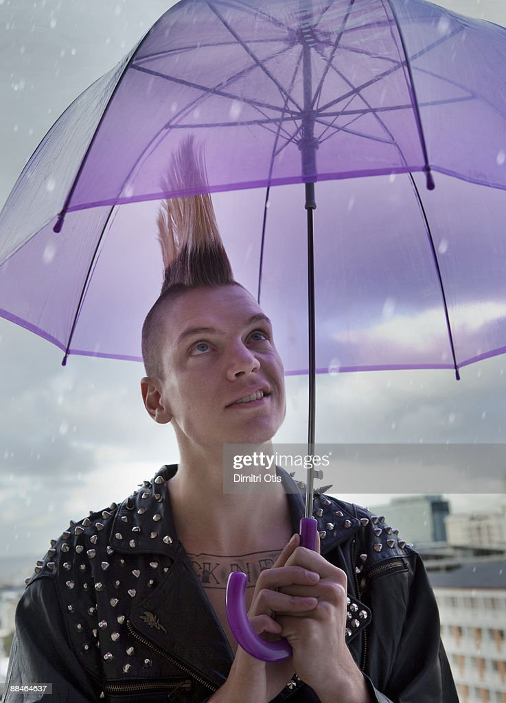 Man with a mohawk under an umbrella : Stock Photo