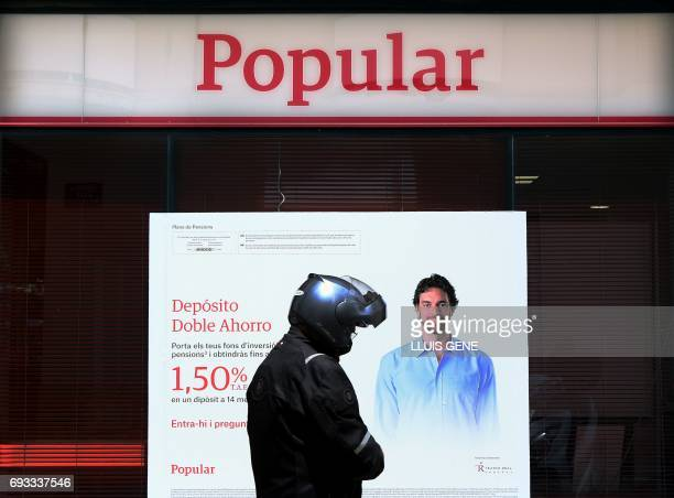 A man with a motorcycle helmet walks in front Banco Popular branch on June 7 2017 in Vilanova i la Geltru near Barcelona after European authorities...