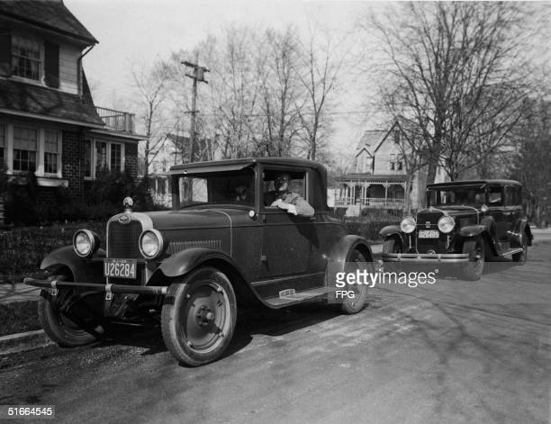 A man with a moustache and glasses looks out from the driver's seat of his 1927 Chevrolet car as he sits by the side of a suburban residential street...
