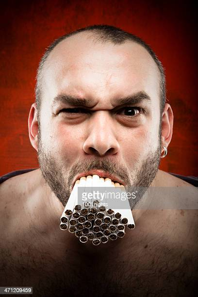 man with a mouth full of many cigarettes - ugly bald man stock photos and pictures