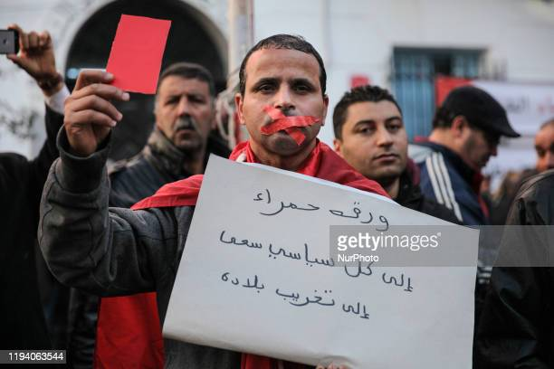 A man with a mouth taped shut holds a placard which reads in Arabic 'Red card to all politicians who aimed to destruct Tunisia' he also shows a red...