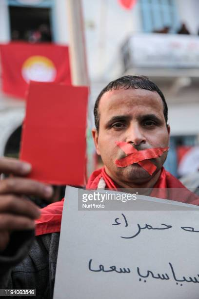 A man with a mouth taped shut shows a red card as a warning against the government as he attends the gathering held outside the UGTT labor union...
