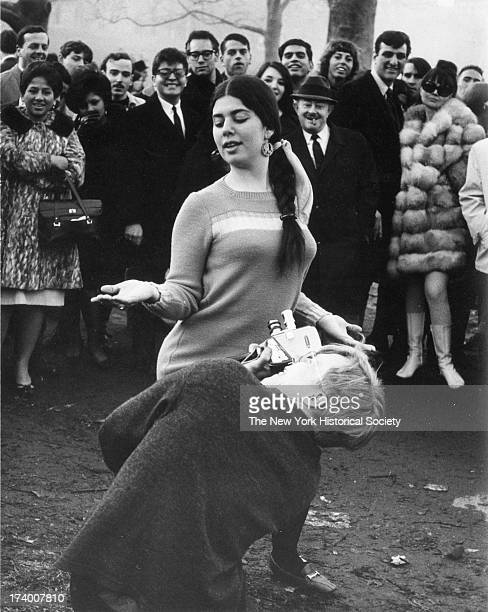 Man with a movie camera films a woman dancing at a 'Bein' in Central Park New York New York March 26 1967