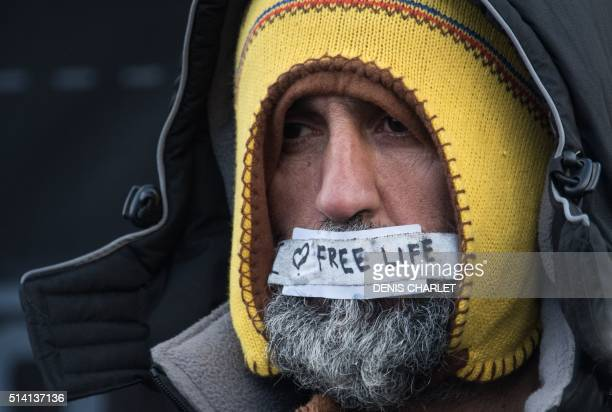 TOPSHOT A man with a note reading 'free life' on his mouth protest against the dismantling of the southern part of the socalled 'Jungle' migrant camp...