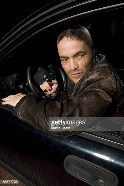 A man with a nylon over his face sitting in a car holding a gun