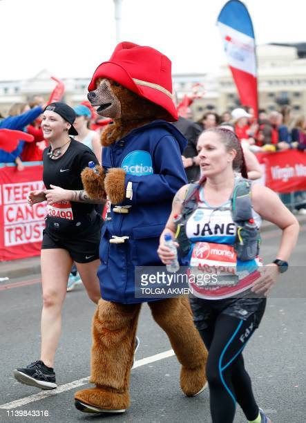 A man with a Paddington bearthemed costume runs across Tower Bridge as he competes in the 2019 London Marathon in central London on April 28 2019 /...