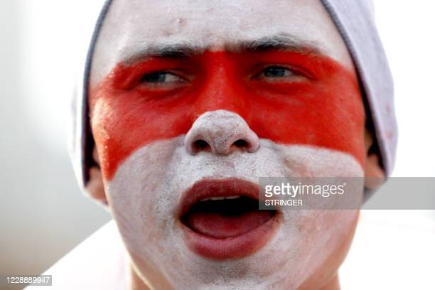 Man with a painted face in the colors of the former white-red-white flag of Belarus takes part in a rally demanding to free jailed activists of the...