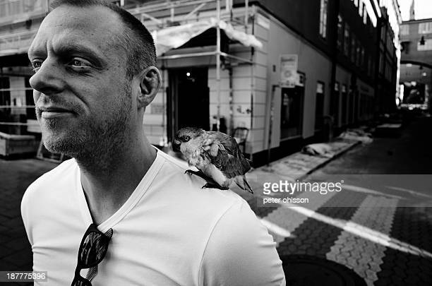 Man with a parrot on his shoulder.