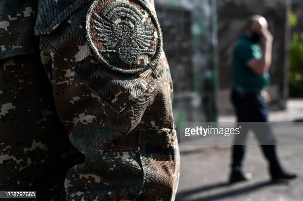 Man with a patch of a Karabakh's Defence Army soldier on his uniform walks in front of a military commissariat in Yerevan on September 30, 2020. -...