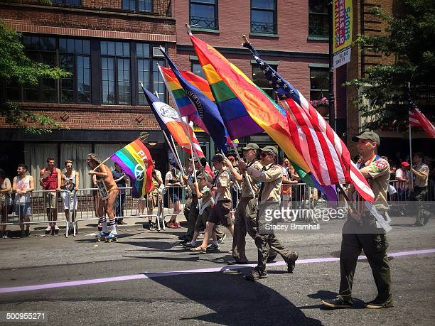 A man with a peace flag roller skates alongside the Boy Scouts of America flag bearers in the New York City Pride Parade