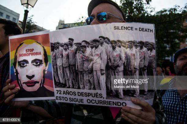 A man with a picture of Vladimir Putting and a picture of a concentration camp during a protest supporting LGTB in Chechnya