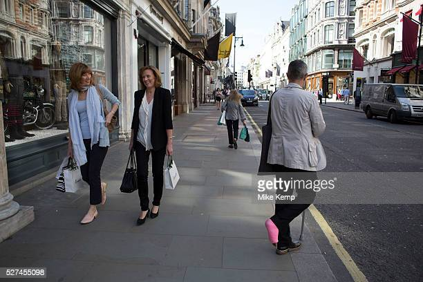 Man with a pink leg cast on New Bond Street London UK