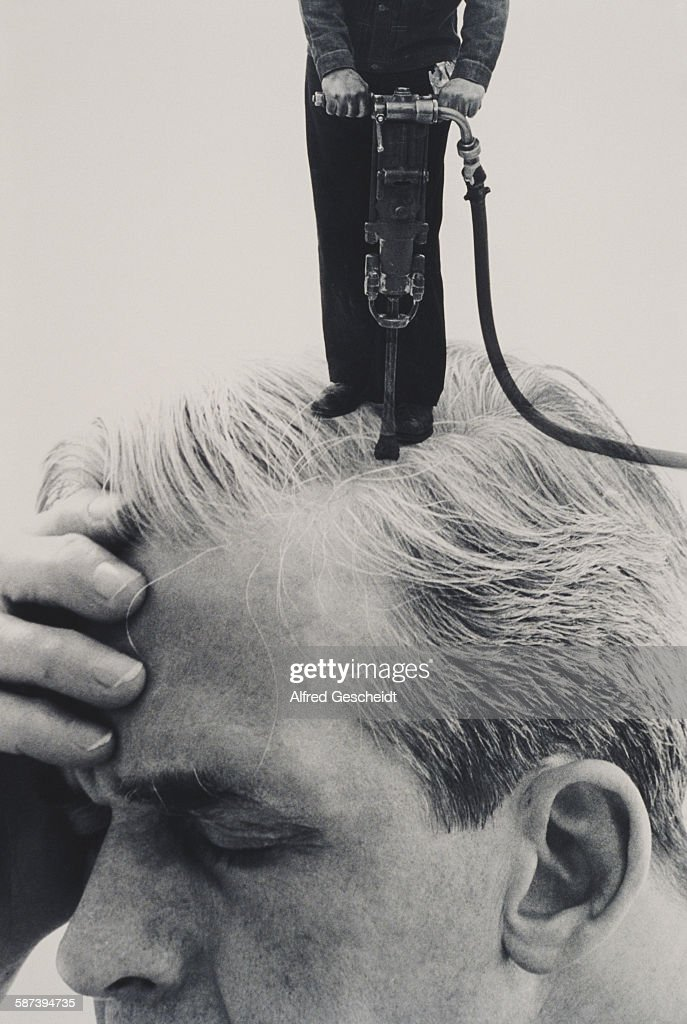 A man with a pneumatic drill drills into another man's head, 1993.