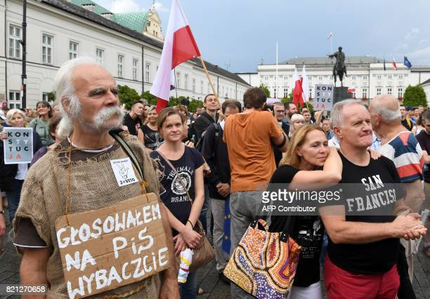 """Man with a poster reading """"I voted for PiS, forgive me"""" attends a protest in front of the presidential palace in Warsaw, as protesters urge Polish..."""