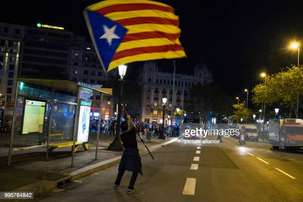 A man with a pro separatist Catalan flag on la rambla street in front of Plaza Catalunya square where citizens were summoned to do a balance of the...