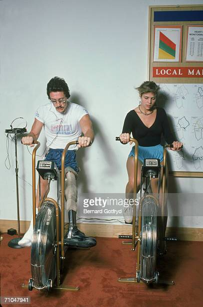 A man with a prosthetic leg and a women exercise on stationary bicycles in a gymnasium early to mid 1980s
