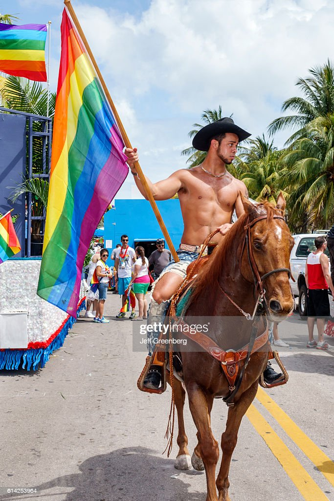 Man With A Rainbow Flag Riding A Horse At The Gay Pride Parade On Ocean