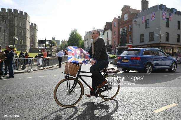A man with a Royal Wedding souvenir flag rides a bicycle past Windsor Castle in Windsor on May 18 the day before the Royal wedding Britain's Prince...