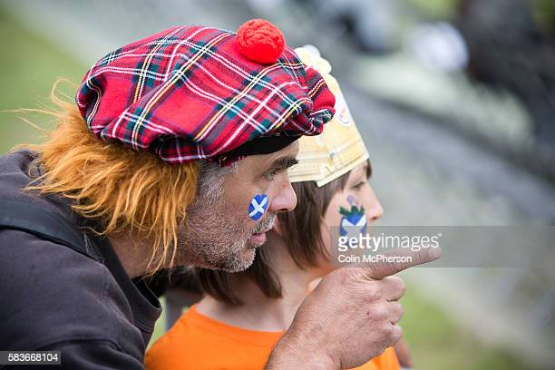 A man with a Scottish Jimmy Wig hat and his son watching the events at Bannockburn Live at Bannockburn Stirlingshire The reenactment marked the 700th...