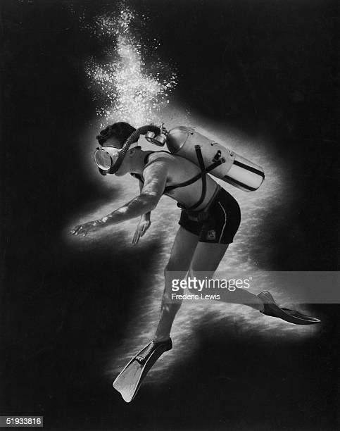 Man with a scuba mask, flippers and aqualung floats underwater in a ghostly haze of bubbles.