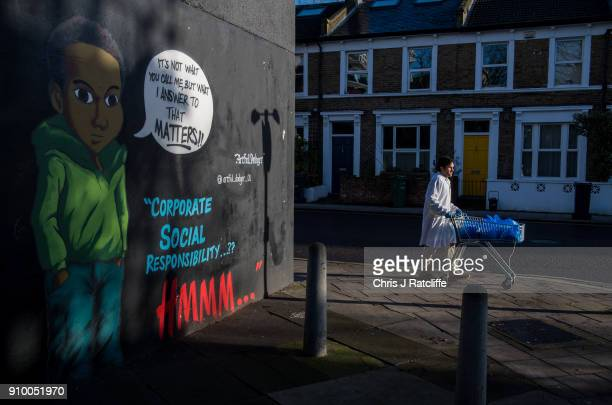 A man with a shopping cart walks past artwork by graffiti artist 'The Artful Dodger' on a wall in Brixton in response to an advert by clothing store...