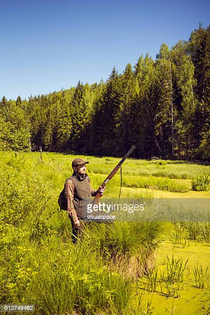Man With A Shotgun Standing In An Open Swamp Scenery