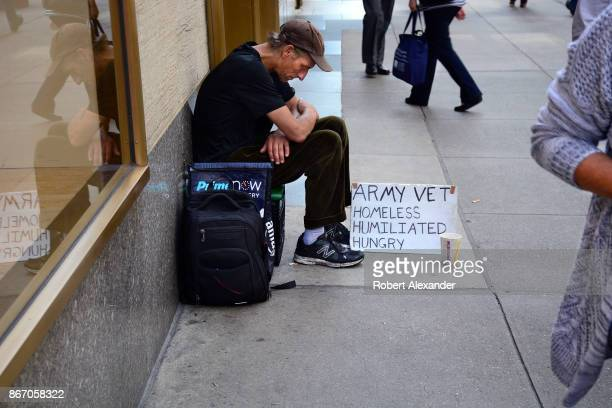 A man with a sign identifying himself as a homeless Army veteran asks for money as he sits on a New York City sidewalk