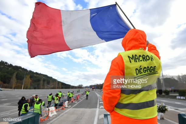 """Man with a sign reading """"Macron resign"""" waves a French flag as """"yellow vests"""" protestors gather to protest against rising oil prices and living costs..."""