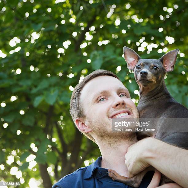 A man with a small dog on his shoulders.