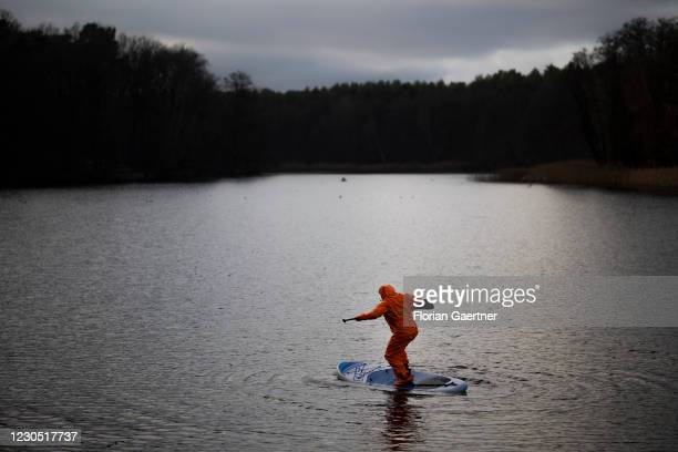 Man with a stand up paddle is pictured at the lake Krumme Lanke on January 10, 2021 in Berlin, Germany.