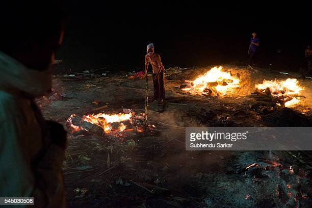 A man with a stick in hand sees that a corpse gets properly cremated at Manikarnika ghat in Varanasi It is a traditional holy place on the banks of...