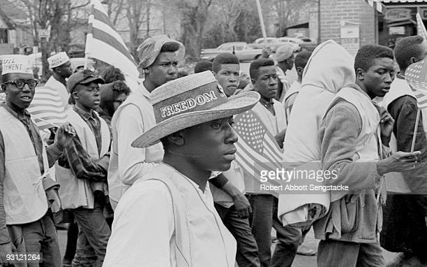 Man with a straw hat that reads 'Freedom' on its band walks with others during on the Selma to Montgomery marches held in support of voter rights,...