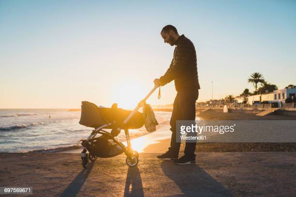 Man with a stroller on the seashore at sunset