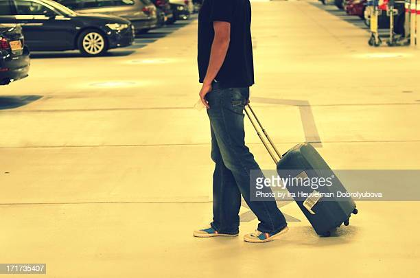 Man with a suitcase in parking lot