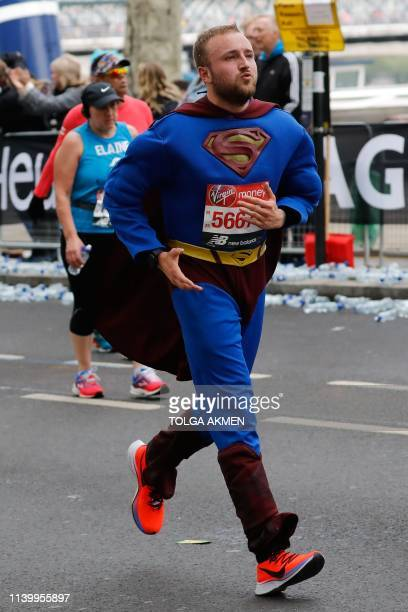 A man with a Supermanthemed costume runs as he competes in the 2019 London Marathon in central London on April 28 2019 / Restricted to editorial use...
