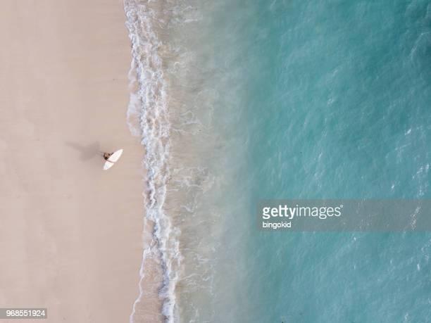 homem com uma pé de prancha de surf na praia olhando para o oceano (de cima) - espuma sintética - fotografias e filmes do acervo