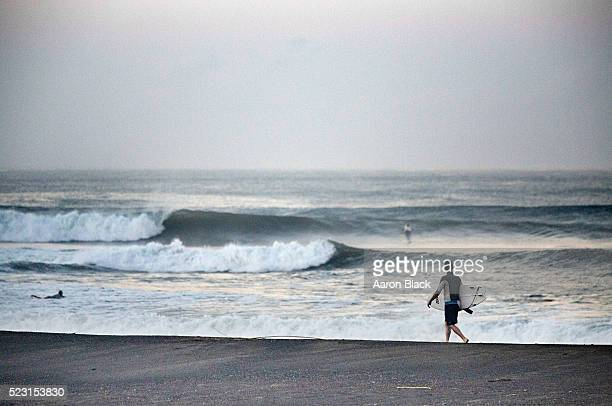 Man with a surfboard walks on beach in front of waves