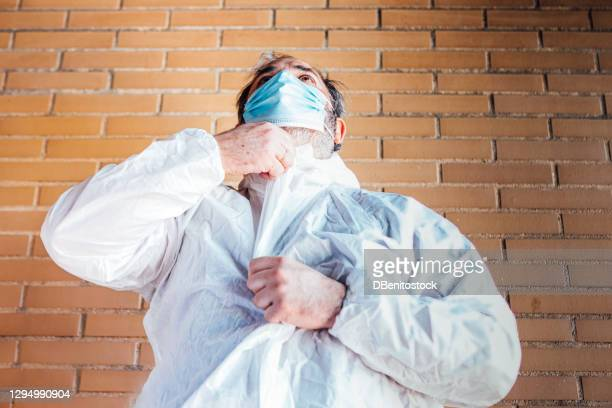 a man with a surgical mask, putting on a ppe to protect himself from covid-19 brick background, to disinfect a house - kontaminierung stock-fotos und bilder