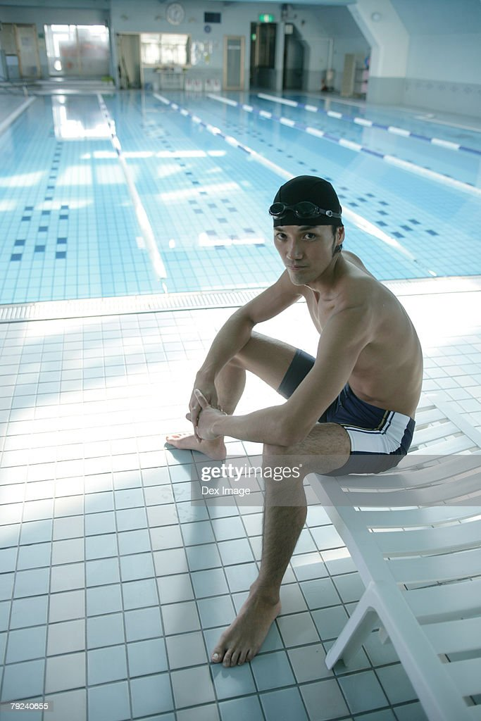 Man with a swimming cap and goggles sitting on a deck chair by the swimming pool : Stock Photo
