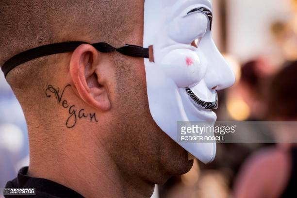 A man with a tatoo reading Vegan wears a Guy Fawkes mask as he takes part in the Global March for Elephants and Rhinos to save elephants and rhinos...