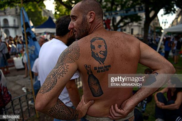 A man with a tattoo depicting Argentinian former President late Nestor Kirchner camps with members of the Tupac Amaru neighborhood association and...