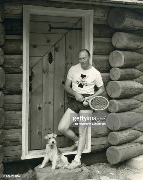 Man with a tennis raquet poses outside log cabin with a dog at his feet, circa 1934.