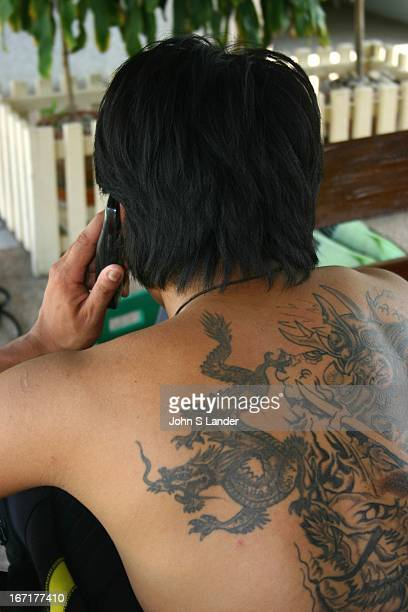 A man with a Thai Dragon Tattoo on his back talks on his mobile phone